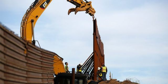 Workers replace sections of the border wall, left, with new sections, right, on Tuesday in Tijuana, Mexico.