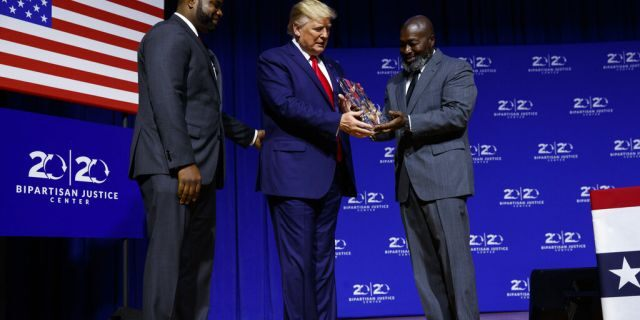 """President Donald Trump is awarded the Bipartisan Justice Award by Matthew Charles, right, one of the first prisoners released by the First Step Act, during the """"2019 Second Step Presidential Justice Forum"""" at Benedict College, Friday, Oct. 25, 2019, in Columbia, S.C."""